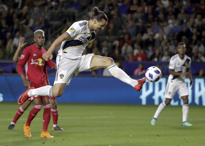 LA Galaxy forward Zlatan Ibrahimovic kicks the ball into the goal during the second half of an MLS soccer match against the New York Red Bulls, in Carson, Calif. The goal was later disallowed. Zlatan Ibrahimovic is returning to the Los Angeles Galaxy. A person with knowledge of the deal confirms the 37-year-old striker will play next season for the Galaxy. The person spoke on the condition of anonymity because the team had not yet formally announced it.
