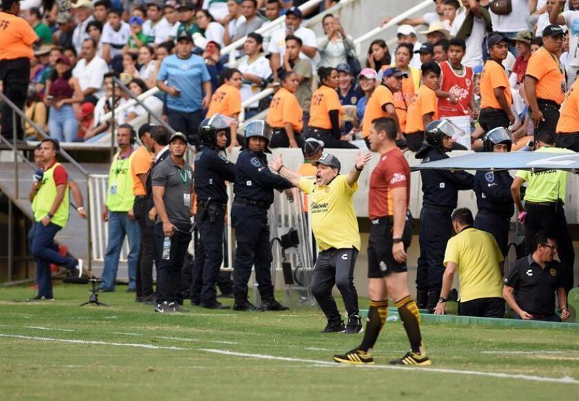 En la imagen el registro del técnico argentino de Dorados de Sinaloa, Diego Armando Maradona (c), quien se enfrentó con seguidores del Zacatepec que le lanzaron un vaso lleno de cerveza. EFE/Archivo