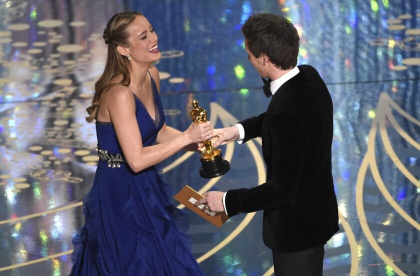 """Eddie Redmayne, right, presents Brie Larson with the award for best actress in a leading role for """"Room"""" at the Oscars on Sunday, Feb. 28, 2016, at the Dolby Theatre in Los Angeles. (Photo by Chris Pizzello/Invision/AP)"""