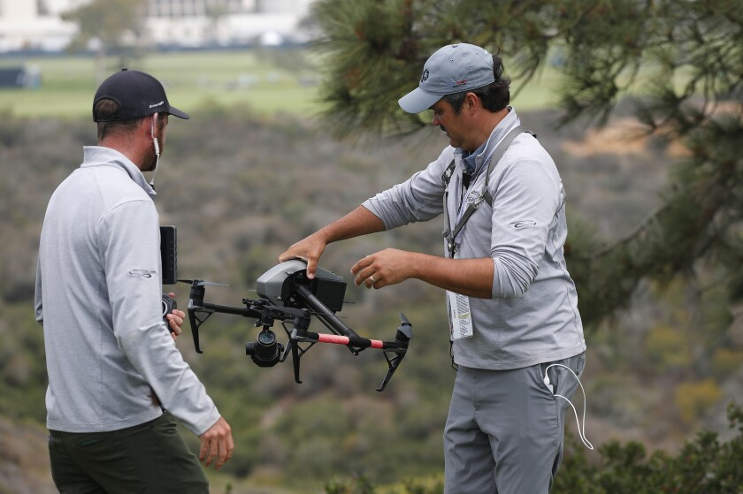 Drone operator Ben McClung picks up a drone used for coverage of the U.S. Open. Tanner Deprin, left, looks on.