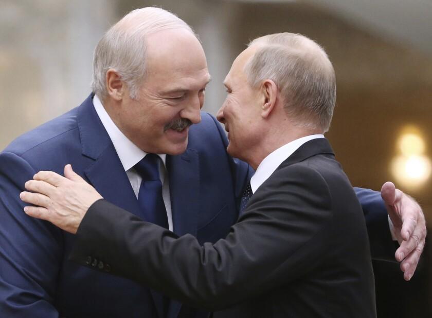 Belarusian President Alexander Lukashenko, left, greets Russian President Vladimir Putin in 2017
