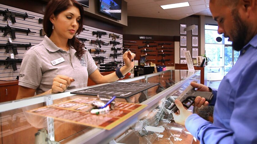 Poway Weapons & Gear is one of the newest businesses in the South Poway Business Park, home to about 400 diverse businesses. In this 2014 photo sales associate Izmir Caro, left, stands by to answer questions as Rudy Avendano of San Diego handles a Glock handgun. Photo by John Gastaldo/U-T San Diego