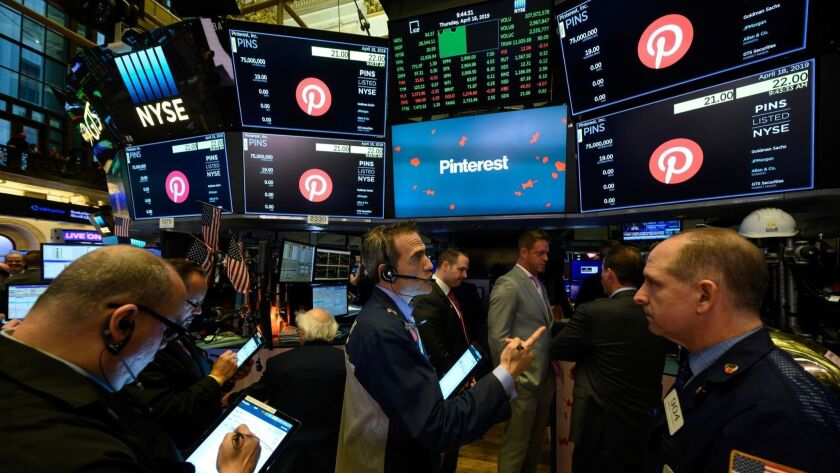 Traders work Thursday at the New York Stock Exchange, where the Pinterest logo is displayed on screens.