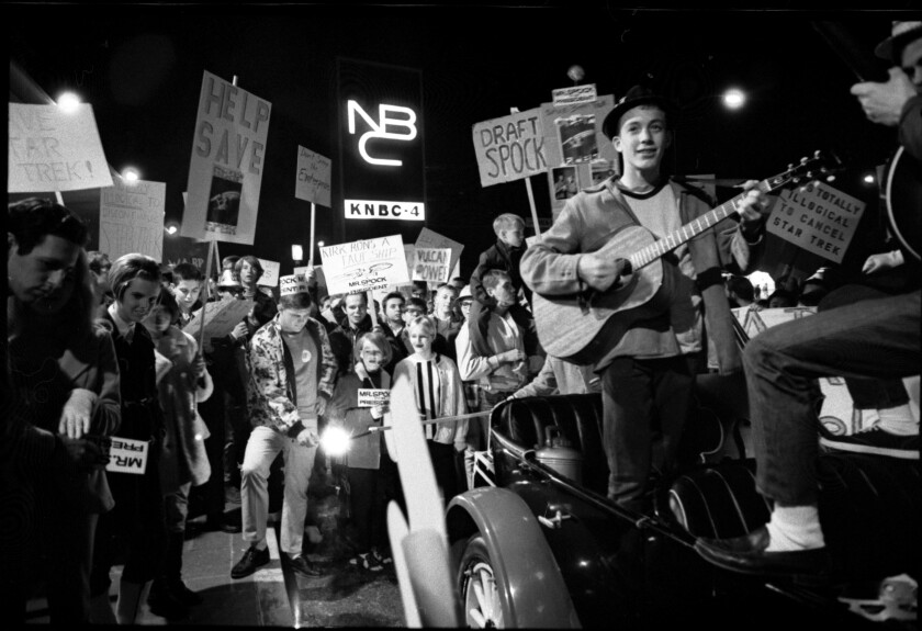 """Young people carry """"Star Trek""""-themed signs. One young man plays a guitar."""