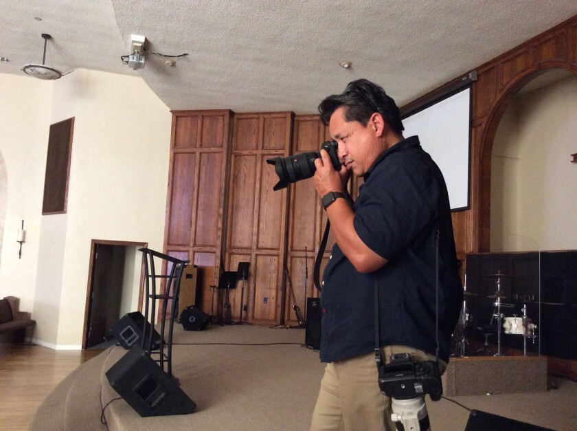 Union-Tribune photojournalist Nelvin Cepeda photographs the subject of a story by reporter Peter Rowe at a church in Chula Vista.