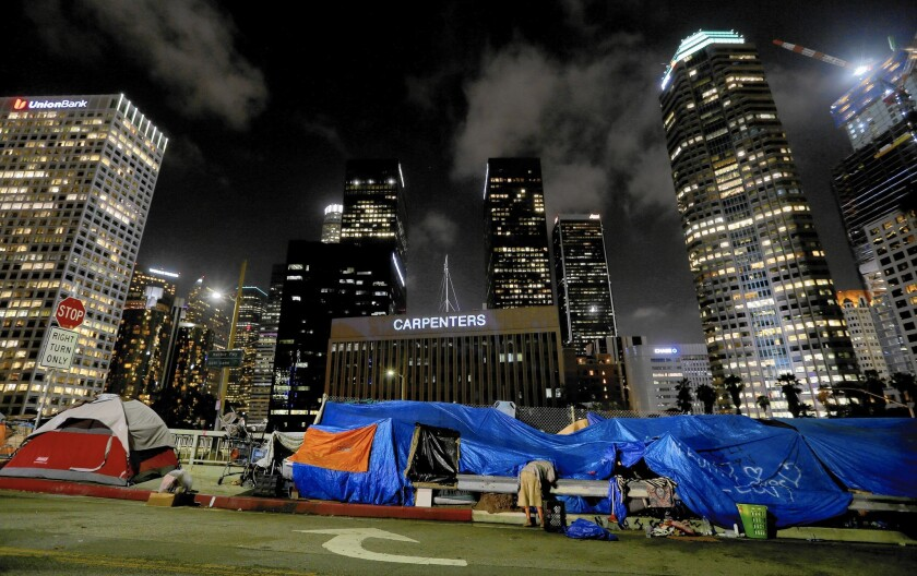 A homeless man prepares to sleep for the night in a streetside encampment beneath the gleaming towers of the financial district in downtown Los Angeles.
