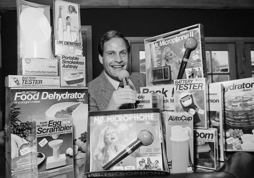 A man surrounded by boxes of such products as a food dehydrator, egg scrambler, microphone and smokeless ashtray