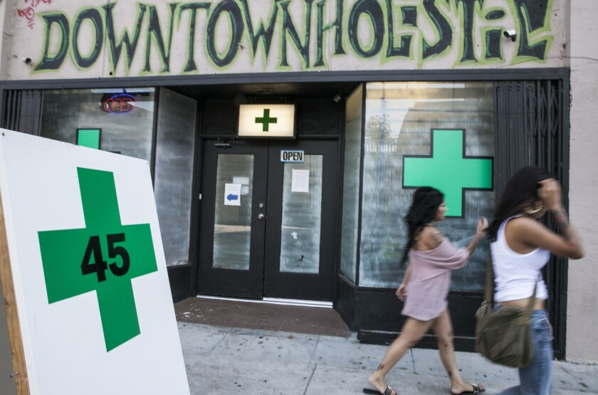 Pedestrians walk past a medical marijuana business in the Echo Park area of Los Angeles in 2012. The L.A. City Council is trying to implement a voter-approved measure to limit the number of pot shops.