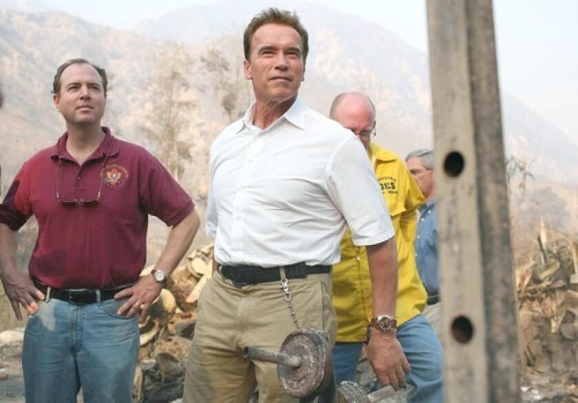 Rep. Adam B. Schiff (D- Burbank), left, and Gov. Arnold Schwarzenegger tour fire damage in Tujunga.