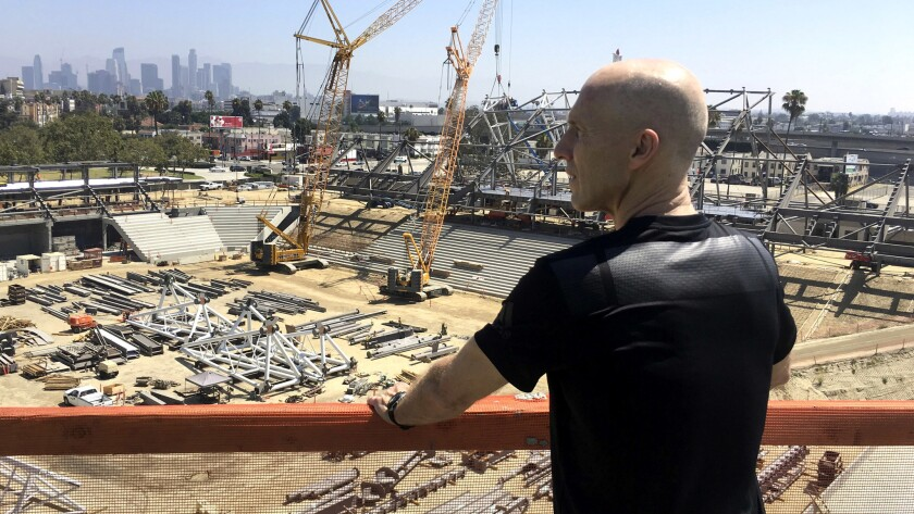 Coach Bob Bradley takes in a view of LAFC's new stadium, which is under construction near the Coliseum.