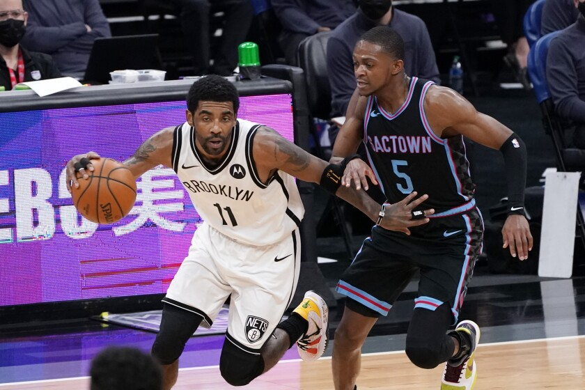 Brooklyn Nets guard Kyrie Irving, left, drives downcourt against Sacramento Kings guard De'Aaron Fox during the first half of an NBA basketball game in Sacramento, Calif., Monday, Feb. 15, 2021. (AP Photo/Rich Pedroncelli)
