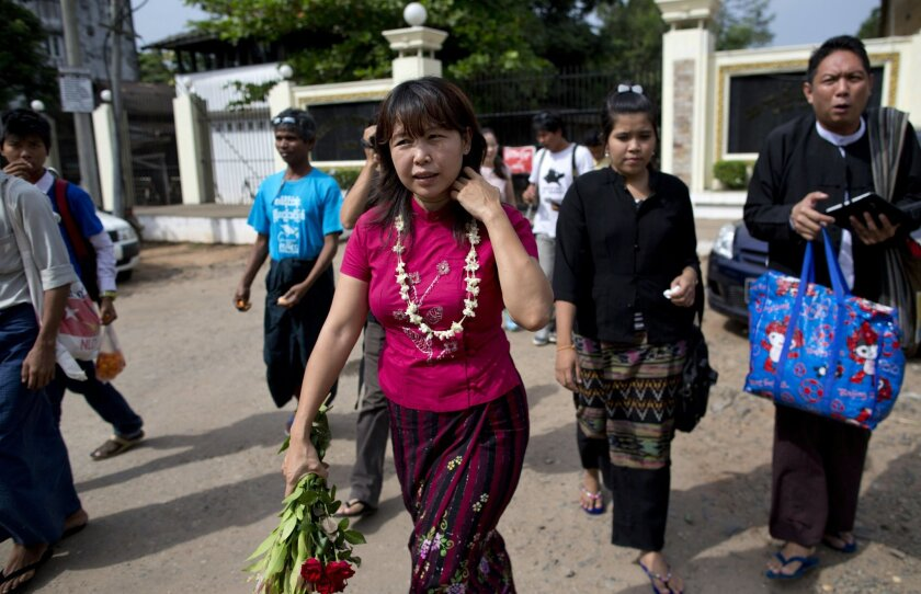 Myanmar civic rights activist Ma Tandar, center with flowers, walks out of Insane prison after receiving a presidential pardon, Wednesday, Dec. 11, 2013, suburbs of Yangon, Myanmar. Myanmar's President Thein Sein has pardoned 44 political prisoners, coinciding with the country's hosting of the Southeast Asian Games. The majority of those freed Wednesday were activists charged under a peaceful assembly law that sets a maximum one-year prison term to people who protest without permission. (AP Photo/Gemunu Amarasinghe)
