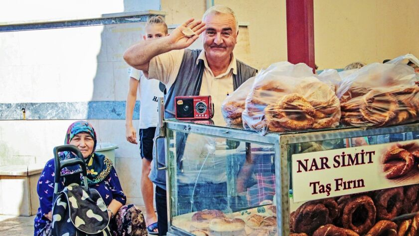 A friendly vendor in Canakkale sells simit bread rings, a favorite street food in Turkey. CREDIT: No