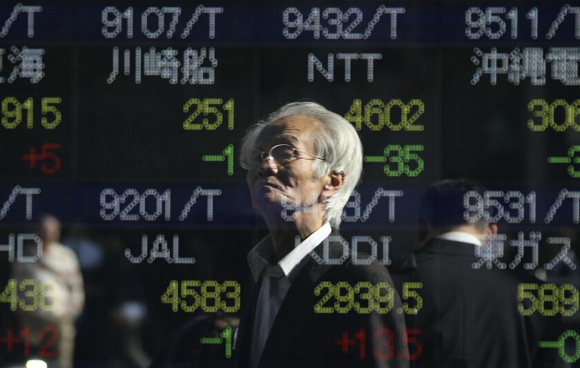 A man is reflected on the electronic board of a securities firm in Tokyo, Japan, Friday, Nov. 6, 2015. (AP Photo/Koji Sasahara)