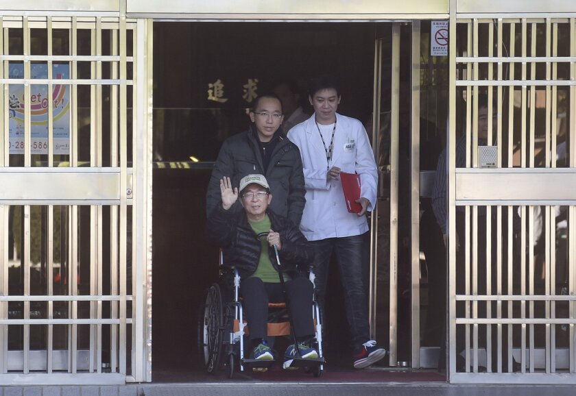 Former Taiwanese President Chen Shui-bian waves as he leaves prison in Taichung, Taiwan. Pushing the wheelchair is his son Chen Chih-chung.