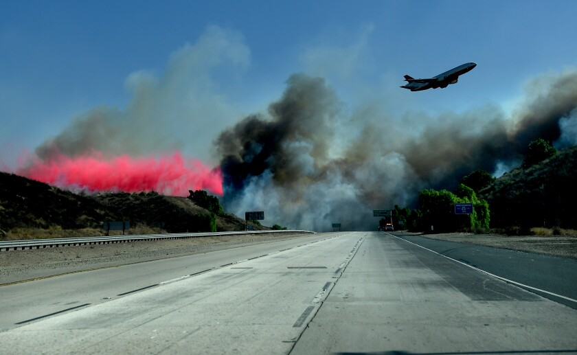 An air tanker drops fire retardant near the 23 Freeway as firefighters make a stand and prevent the Easy Fire from burning into Moorpark Wednesday.