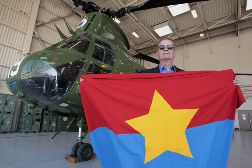 Retired Marine CH-46 pilot Carl Stoehr holds the Viet Cong flag he and his crew took while hovering a CH-46 next to it during a rescue mission in Vietnam, January, 1968.