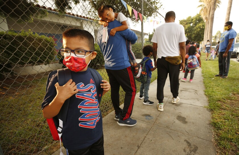 Students and parents wear masks in a line outside a school