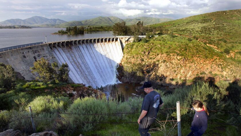 Kevin Allison of Paradise Valley along with his daughter, Brittany take a hike to get better advantage point of Lower Otay Reservoir spilling over the gate.