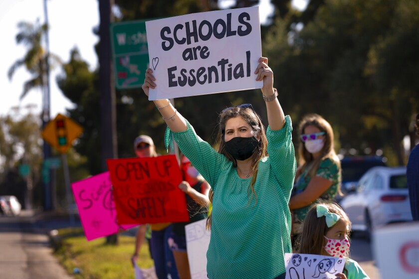 Parents and protesters held signs calling for San Diego Unified schools to reopen in September
