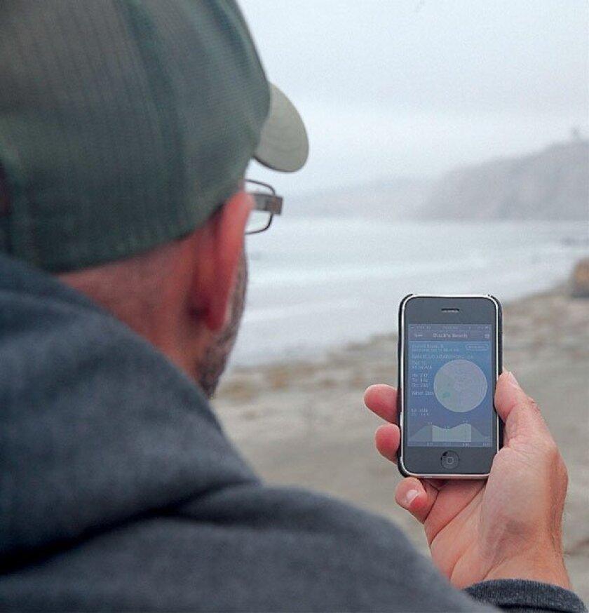 Ed Esquenazi checks out the SurfExplorer USA iPhone app near Scripps Pier. Photo: Kris Schlesser