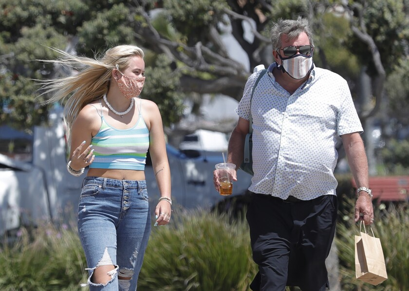 Megan Harris and her father, Ray, walk the boardwalk in Laguna Beach on Thursday.