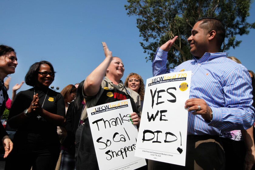 United Food and Commercial Workers Union on Monday released a report showing steep declines in wages since 1999. Here, Vons checker Angela Baker and Ron Solano, high-five following the decision to not go on strike Sept.20, 2011.