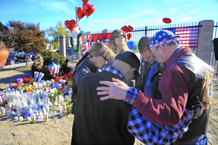Riders from the Christian Motorcycle Assn. in San Bernardino gather in prayer at a makeshift memorial for the 14 individuals gunned down at the Inland Regional Center.
