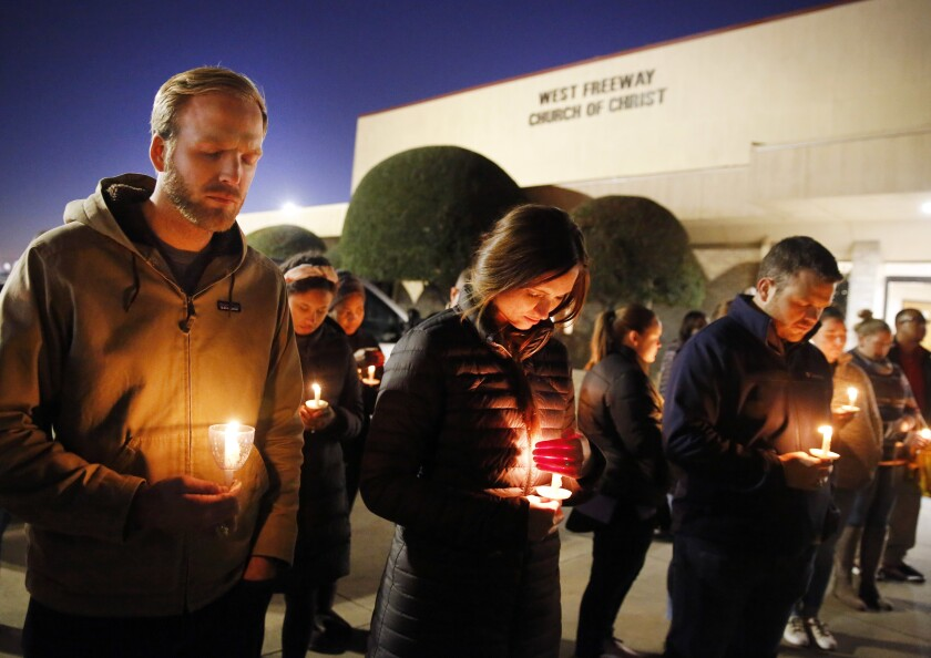 Matt Pacholczyk, left, and his wife, Faith, stand outside West Freeway Church of Christ for a candlelight vigil in White Settlement, Texas, on Monday.