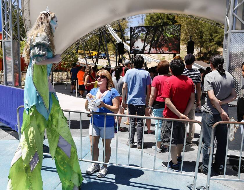 Flora the Fairy talks with Robyn Webb, a visitor to Magic Mountain. Six Flags is also adding an interactive game for waiting guests at all of its parks.
