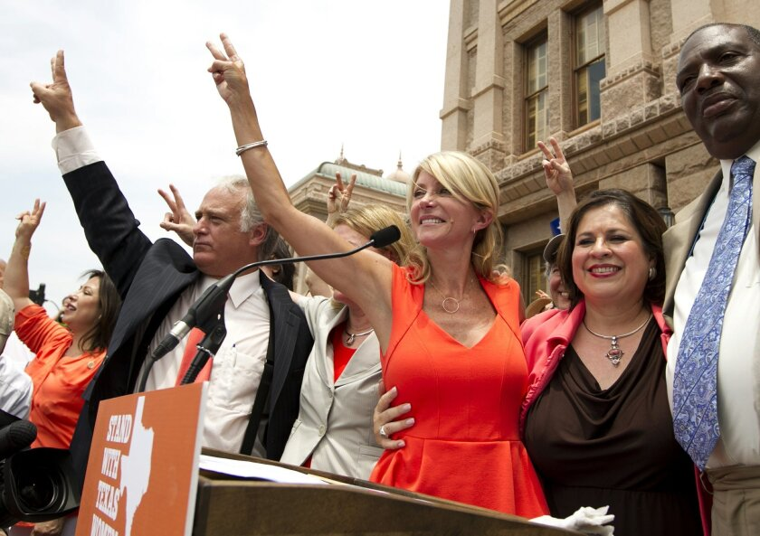 FILE - In this July 1, 2013, file photo, Democratic state senators, from left, Kirk Watson, Wendy Davis, Leticia Van de Putte and Royce West participate in a pro-abortion rights rally at the state Capitol in Austin, Texas. Davis and Van de Putte are going for a new kind of history in the U.S.: Winn