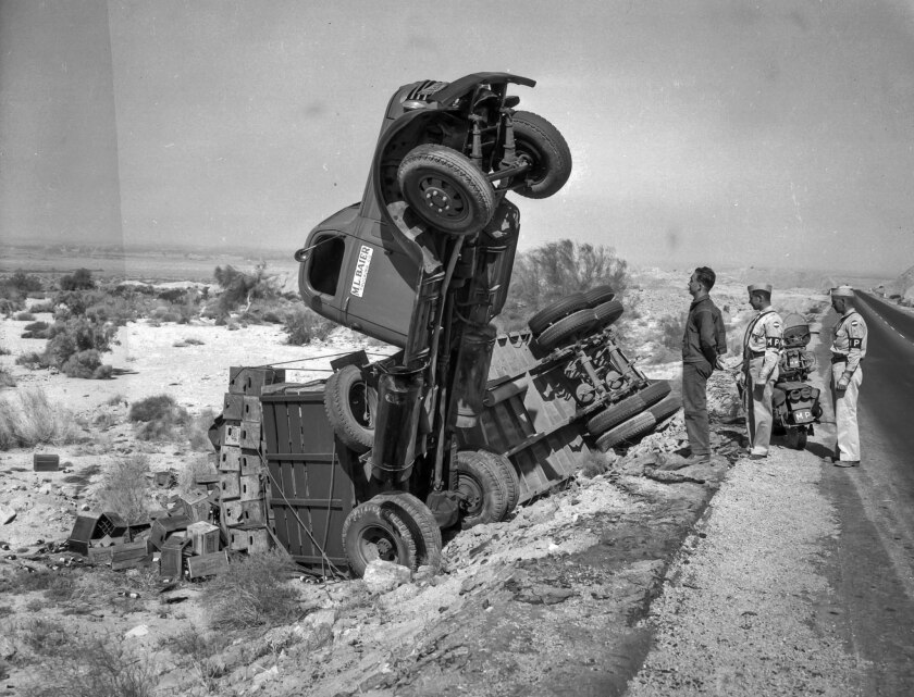 June 6, 1943: Driver E.L. Bohanon and two Army MPs survey the losses following truck overturned on h