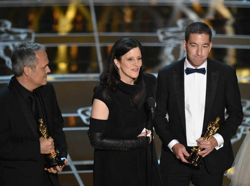 """Dirk Wilutzky, from left, Laura Poitras and Glenn Greenwald accept the award for best documentary feature for """"Citizenfour"""" at the Oscars on Sunday, Feb. 22, 2015, at the Dolby Theatre in Los Angeles. (Photo by John Shearer/Invision/AP)"""