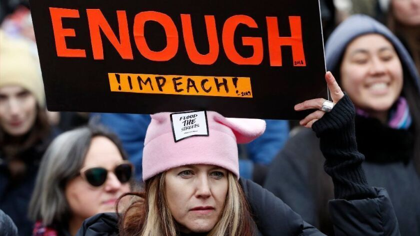 A woman holds a sign expressing support for impeaching President Trump at a rally organized by Women's March NYC in New York on Jan. 19.