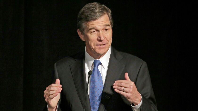 In a June 2016 file photo, then-North Carolina Atty. Gen. Roy Cooper speaks during a forum in Charlotte, N.C.