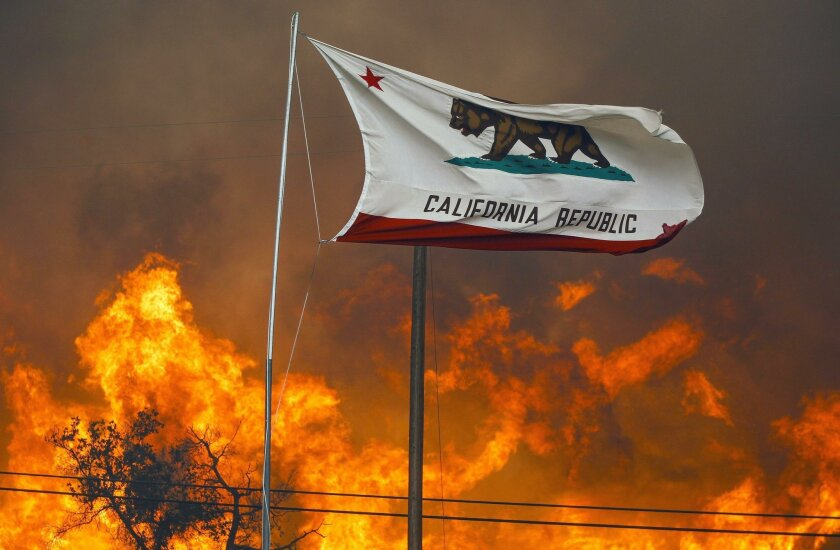 The California state flag flies next to a home on Highway 94 south Potrero on Monday as huge flames roar behind it.