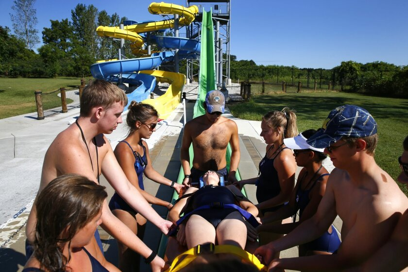In this Aug. 5, 2015, photo, lifeguards simulate a shallow water rescue on a backboard from a water slide at the Rolling Hills Water Park in Ypsilanti, Mich., Wednesday, Aug. 5, 2015. Concern is growing about risks present even when most waterpark water is shallower than 3 feet. (AP Photo/Paul Sancya)