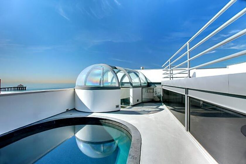 Stairs from the master suite ascend to a glass-enclosed landing on the rooftop deck.