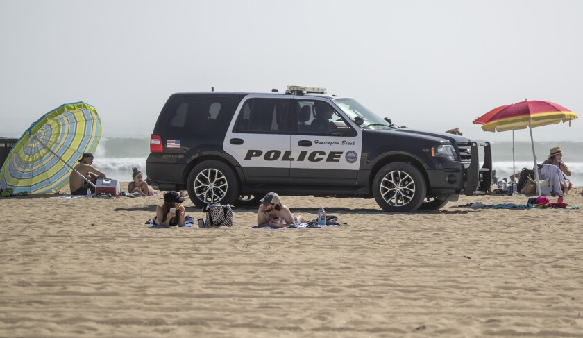 Huntington Beach police patrol the beach near the pier Saturday as thousands of people enjoy a warm, sunny day amid stay-at-home and social-distancing mandates to curb the coronavirus outbreak.