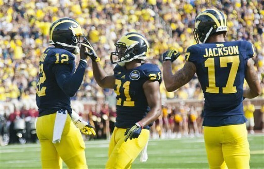 Michigan quarterback Devin Gardner (12) abd wide receivers Jeremy Gallon (21) and Jeremy Jackson (17) celebrate a touchdown in the second quarter of an NCAA college football game against Central Michigan, Saturday, Aug. 31, 2013, in Ann Arbor, Mich. (AP Photo/Tony Ding)
