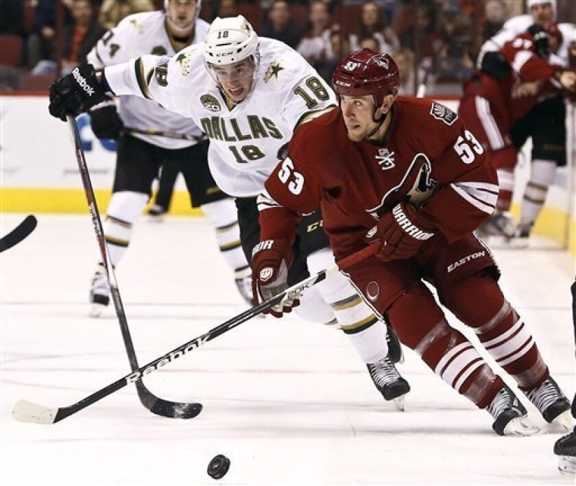 Phoenix Coyotes' Derek Morris (53) tries to keep the puck away from Dallas Stars' Reilly Smith (18) during the first period of an NHL hockey game Saturday, Feb. 2, 2013, in Glendale, Ariz. (AP Photo/Ross D. Franklin)