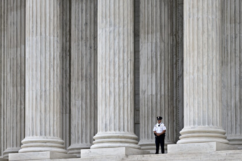 A police officer is dwarfed amid the marble columns of the Supreme Court in Washington on Oct. 7.