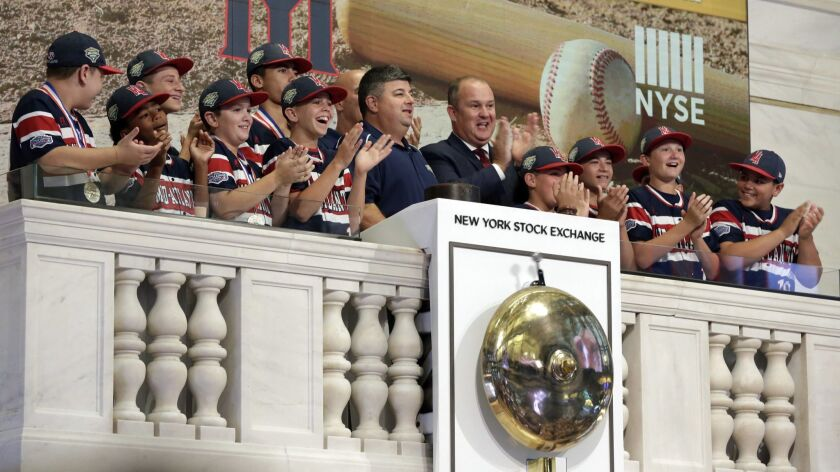 Members of the Mid Island Little League team from Staten Island, N.Y., applaud as their manager rings the New York Stock Exchange opening bell Aug. 31.