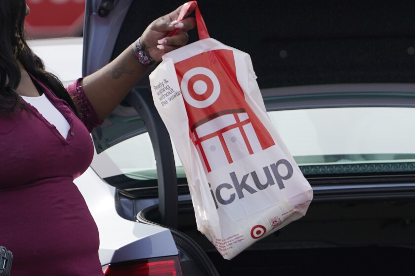 A Target employee places a curbside pickup purchase into the trunk of a customer in Jackson, Miss., Thursday, Nov. 5, 2020. After a weak start to the holiday season for many mall-based retailers, the strugglers are making their final push in the final days before and the week after Christmas. Many are stepping up discounts while heavily promoting curbside pickup as a way to get shoppers, worried about being infected with the virus, to visit their stores. But experts believe that any burst of sales will be too little and too late to save some stores. (AP Photo/Rogelio V. Solis)