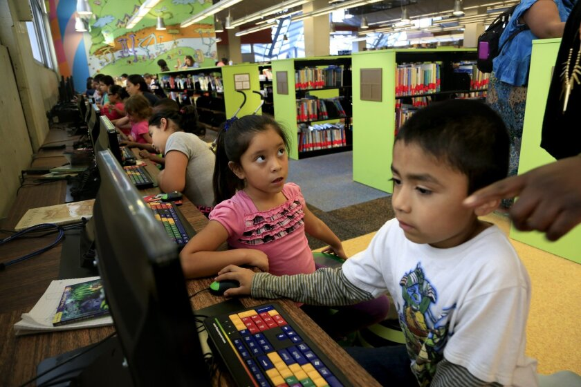 Kimberly Velediaz, 7, center, in pink, and Sylvester Velasquez, 6, make use of the computers in the children's area of the San Diego Central Library.