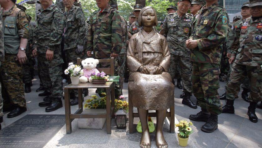 SEOUL, SOUTH KOREA - MAY 23: South Korean Vietnam War veterans stand beside a comfort women statue
