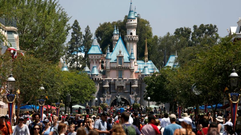 A study found that 73% of workers who were surveyed said they don't earn enough to pay for basic living expenses. Above, guests crowd Main Street in front of Sleeping Beauty Castle at Disneyland in June 2017.