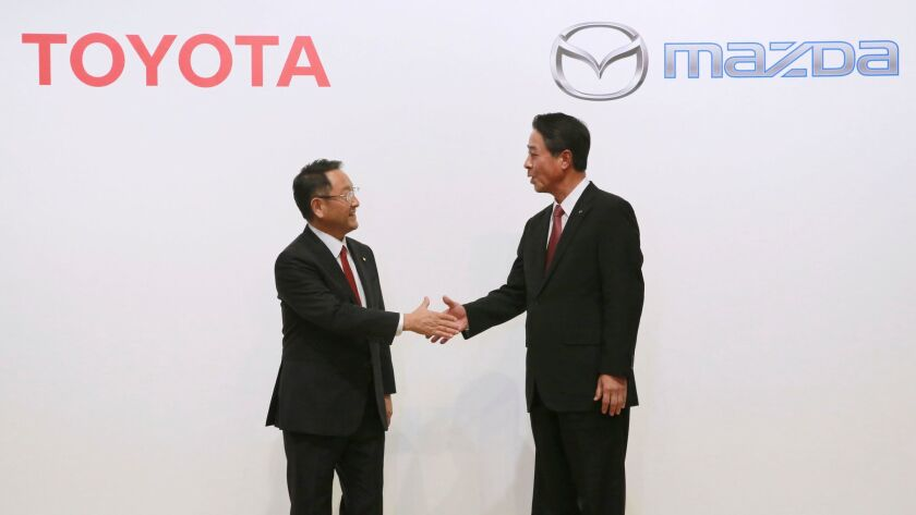 Toyota President Akio Toyoda, left, and Mazda President Masamichi Kogai shake hands in August 2017.