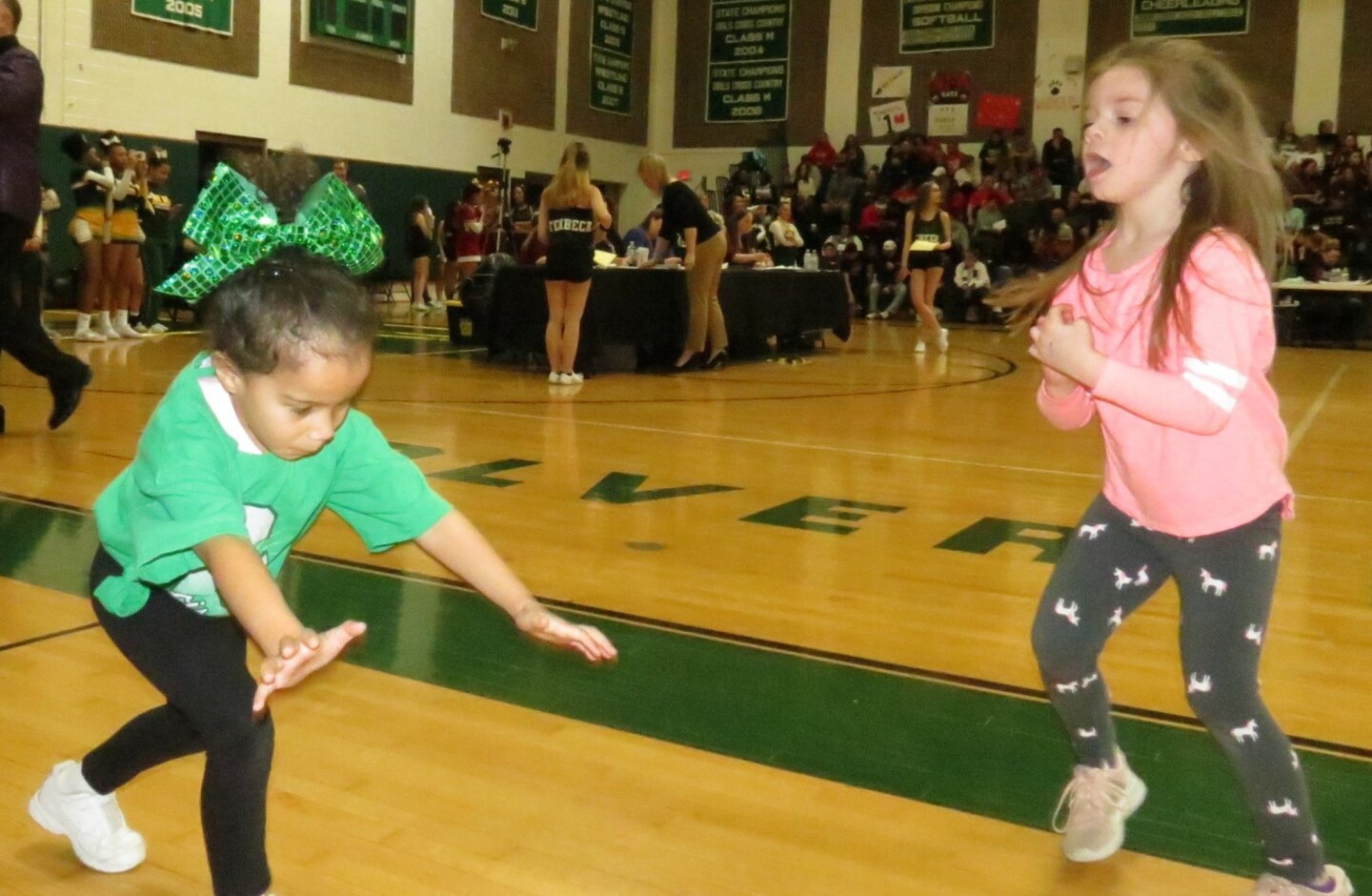 Budding cheerleaders Jaidyn, 5, and Shelby, 4, practice on the sidelines of the Wolverines Pride cheer competition.