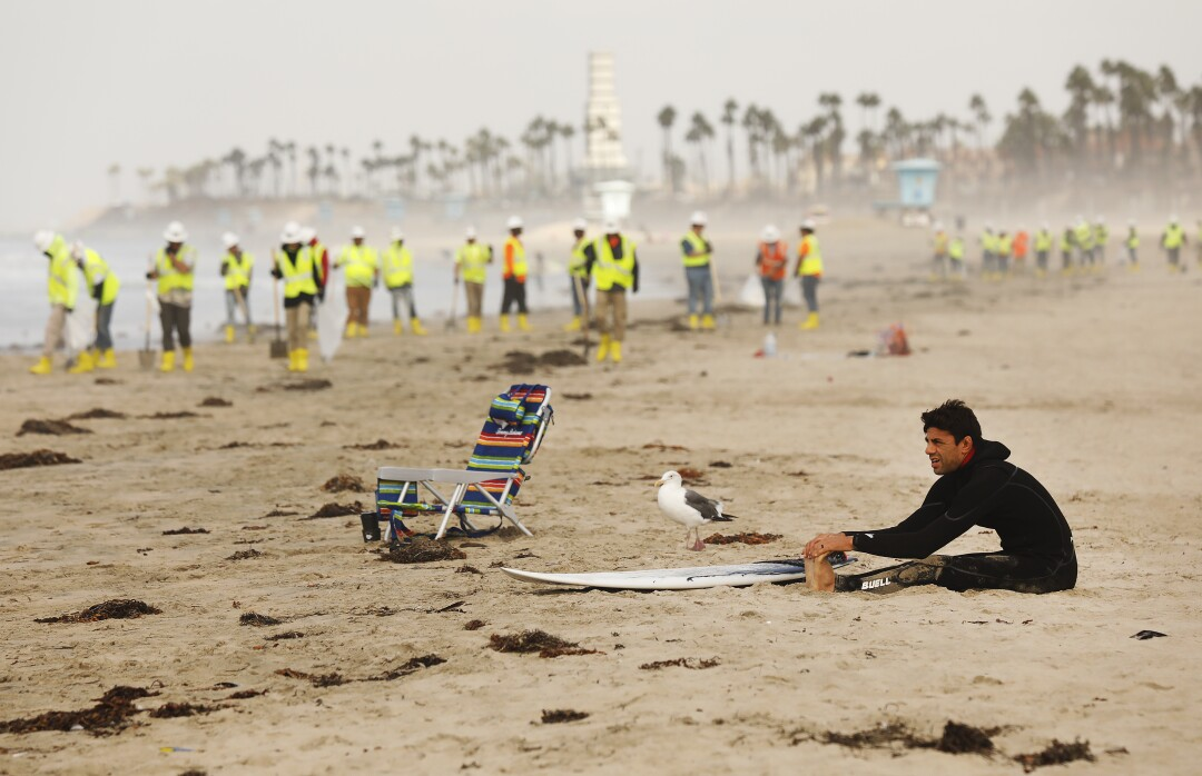 A surfer stretches with a cleanup crew in the background